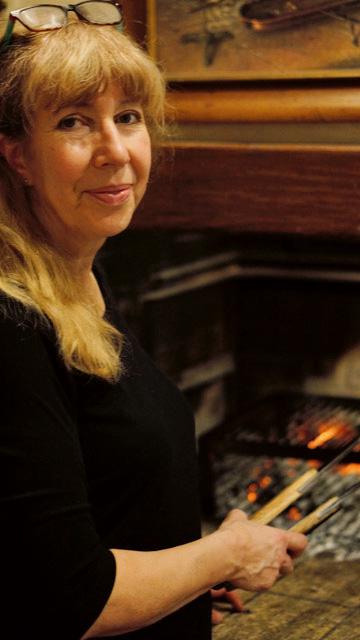 Esther Villiger legt in der Gaststube einen Braten über die Glut.