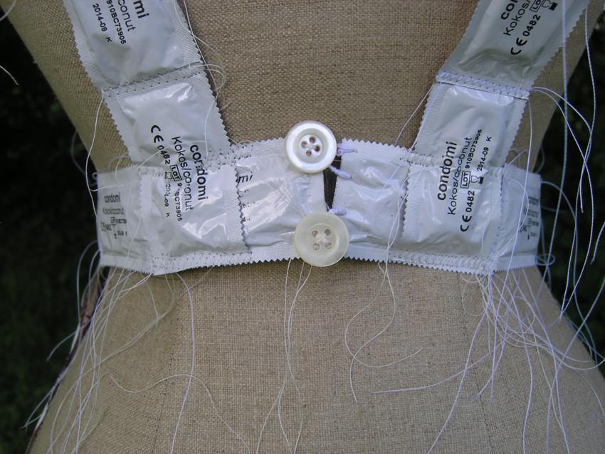 """Eva Hradil """"schürzen"""" 2010, Kondome in Verkackung, Textilien, Nähseide, Knöpfe, Detailansicht"""