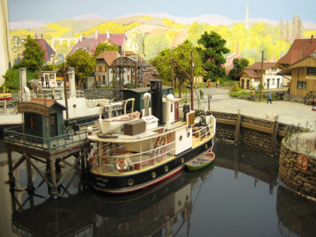 Der kleine Frachter lädt gerade Frachtgut am Holzsteg im Hafen Engen