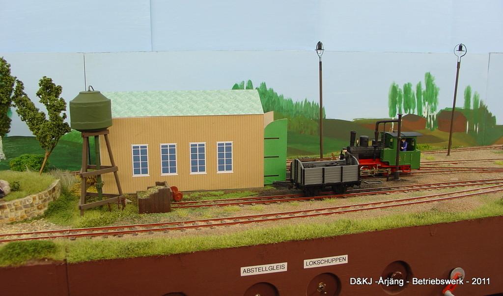 Das Gleis im Vordergrund führt weiter zum Sägewerk. Neben dem Lokschuppen hat entweder der Kohlewagen oder ein leerer Holzwagen Platz.