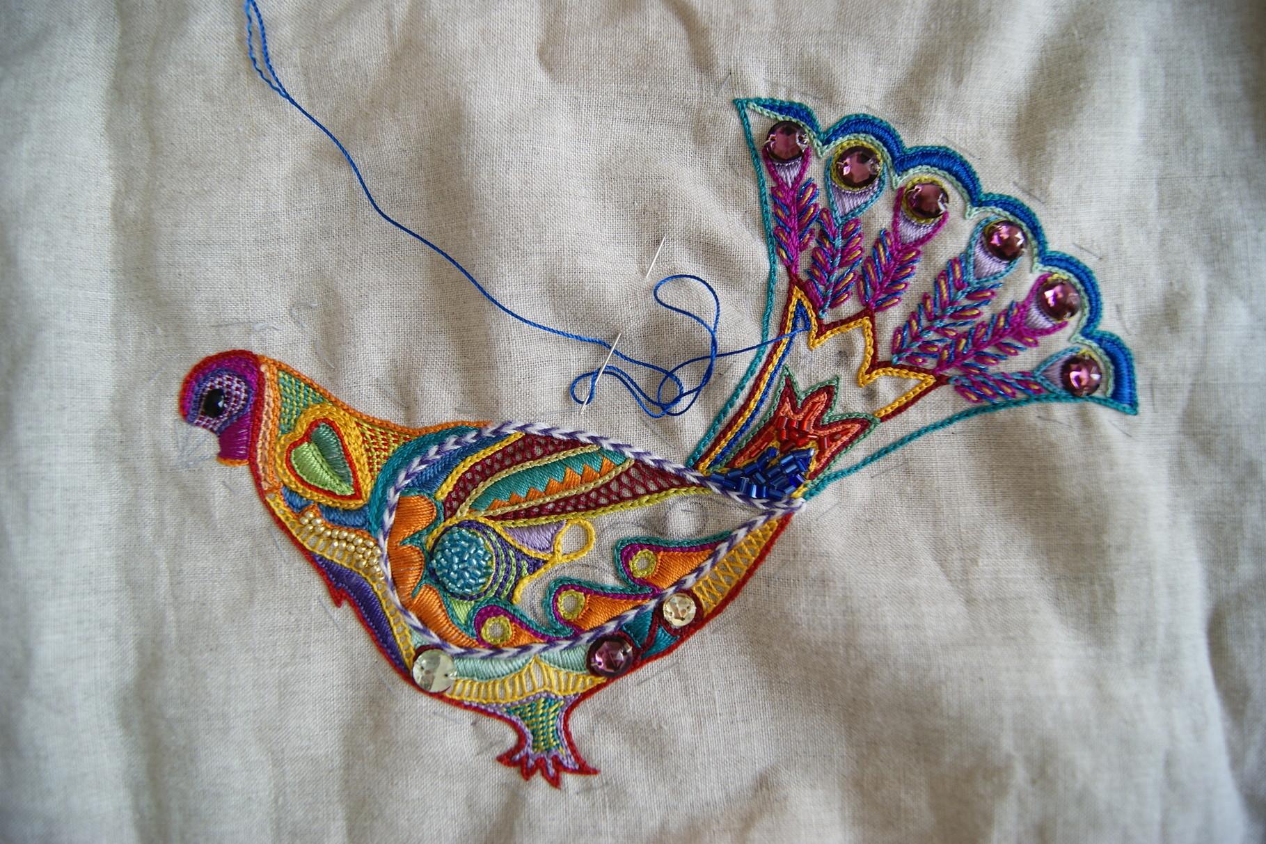 oiseau central brodé en premier sur une pièce de lin à part.