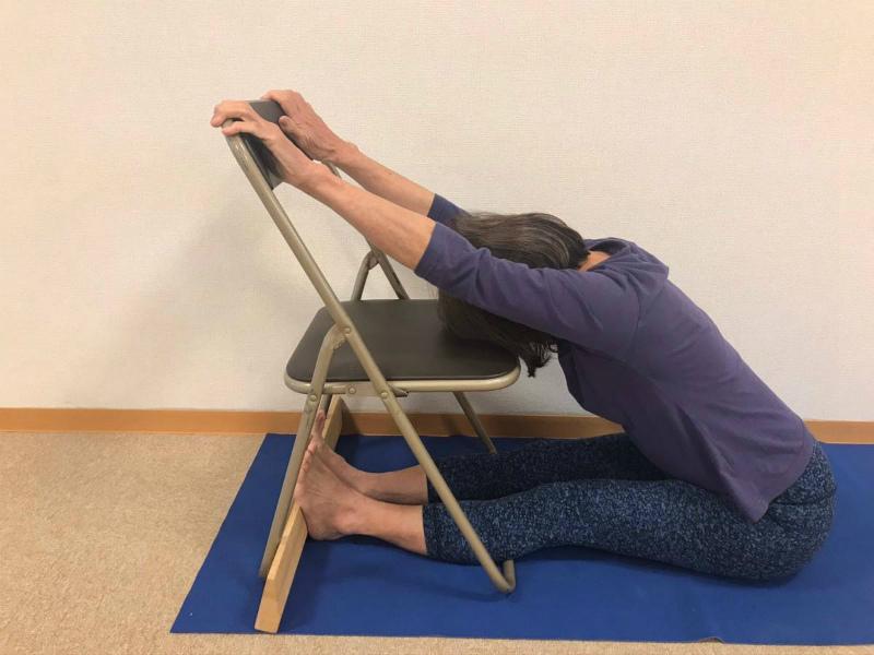背中が丸くなる人は写真のように椅子などを使い、両足裏で何かを押して、 頭を椅子に預けて上体が伸びることを練習します