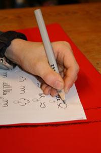 Linke Kinderhand beim Schreiben in der Linkshänderberatung.