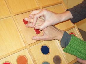 Ansicht zwei Hände von Ergotherapeut und Patient im Rahmen von kognitiv-therapeutischen Übungen nach Perfetti