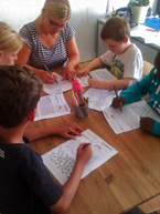 Kinder am Tisch sitzend, betreut von einer Ergotherapeutin, bei einer Übung im Rahmen des Marburger Konzentrationstrainings.