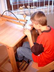 Junge am Tisch sitzend bei einer Übung der sensorischen Integrationstherapie