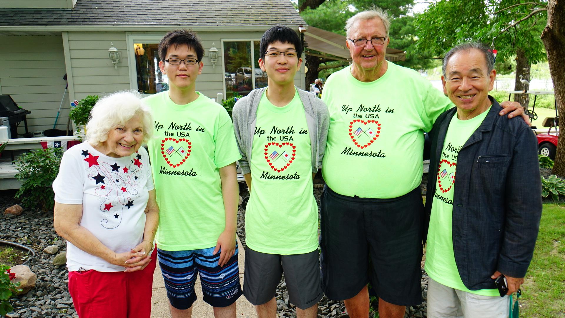 7,000坪、湖つきガイさん宅の庭先で、いただいたTシャツを着てご夫妻とともに(ミネソタ州)