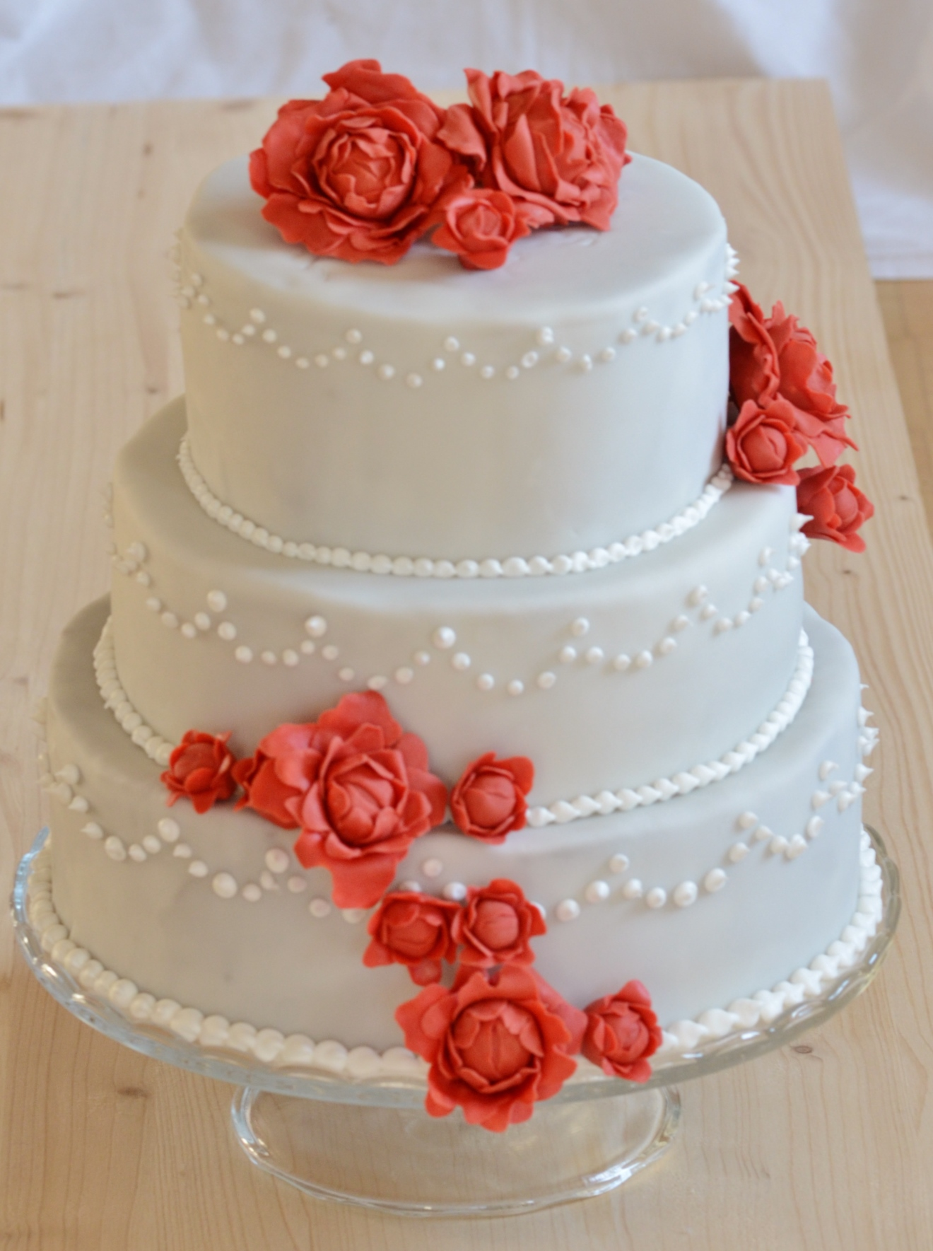 Hochzeitstorte mit roten Pfingstrosen und royal icing