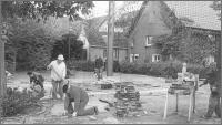 """Ahsener Motto """"Wir packen selbst an"""" Bei der Gestaltung des Dorfplatzes v.l.n.r.: Bernhard Möllmann, Willi Rehr, August Hans und an der Schneidemaschine Heinz Schneider"""