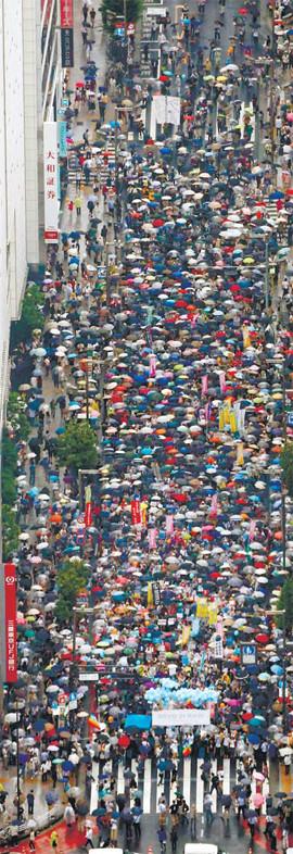 지난 6일 비가 쏟아지는 가운데 도쿄 신주쿠 번화가에서 열린 안보법 반대집회에 1만2000여명의 시민이 모인 광경.  도쿄=AP연합뉴스
