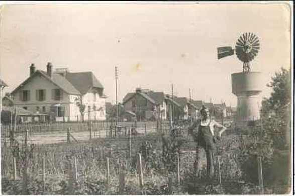Col Guyon - Henri Guyon dans son jardin devant un château d'eau avec son éolienne