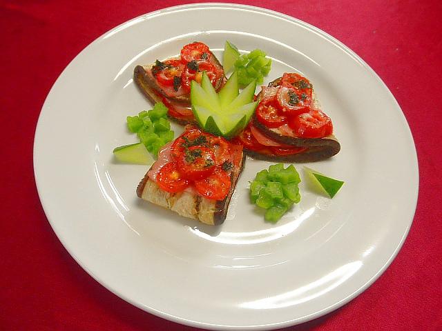 #ナスのトマトチーズ焼き #ナスを5mmくらいに切り塩を散らしアクぬきします #ナスにトマトを並べオーブンで焼きます #焼いたナスにベーコンをのせ粉チーズを散らし #トマトをのせ再びオーブンで5分焼きます #あしらいはゆでツルムラサキ #キュウリを使用
