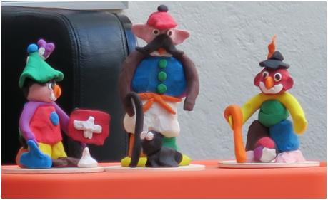 Drei verschiedene Tonfiguren aus drei gleichen Sortimenten von farbigem Ton. Symbol dafür, dass Sageninhalte von jedem Sagenerzähler unterschiedlich gestaltet werden.