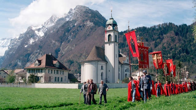Auf dem Weg zum Schlachtdenkmal über die Sändlenwiese, im Hintergrund die St. Hilariuskirche und das Pfarrhaus. (Foto: M. Hauser, Zug)