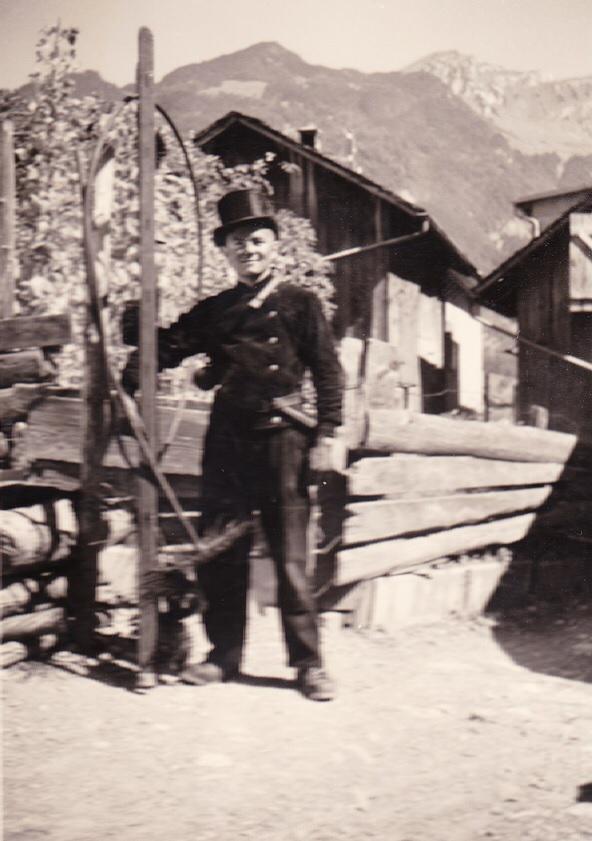 """Archivbild: Der junge Hans Tschudi in """"Berufsuniform"""" und mit den Kaminfegerutensilien, vermutlich im Dorfquartier """"Loch"""", im Hintergrund der Obstock und Nüenchamm, Mollis. (Foto: Margrit Neeracher)."""