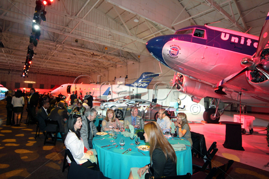Dinner party at an airplane hangar.