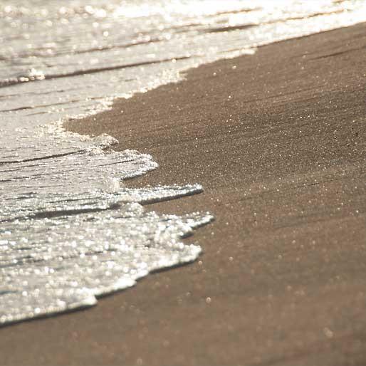 Das Auslaufen der Wellen am Sandstrand