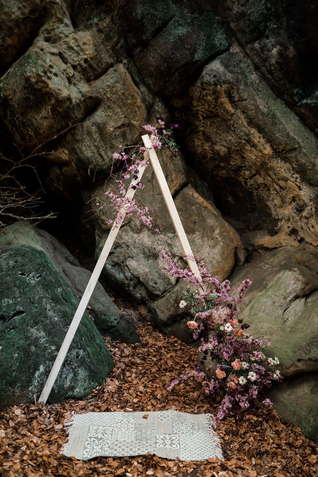 Traubogen mit Blumendekoration vor Felsen, Teppich