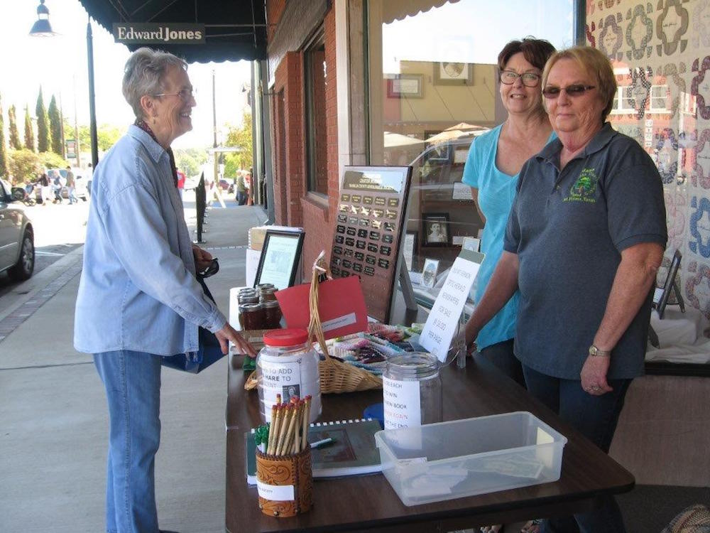 Volunteers Jana Capps & Linda West welcome Beverly Morris to CountryFest 2016