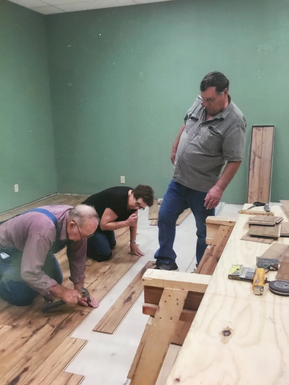Flooring started! Wayne Bryan, Saundra & Charles Dunn placing flooring over wood floor (flooring donated by Lowe's), July 2017