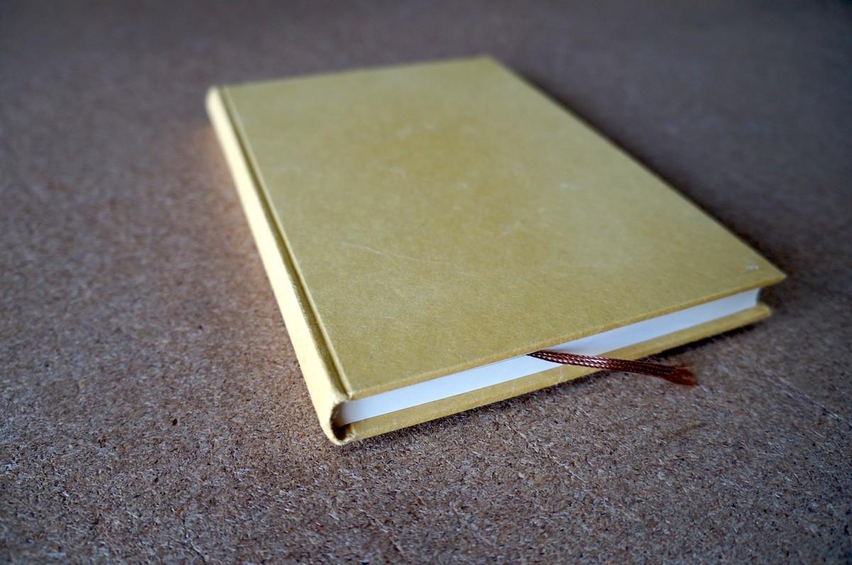 表紙が薄い繊維が入りのからし色和紙を使った手製本の丸背上製本ノート