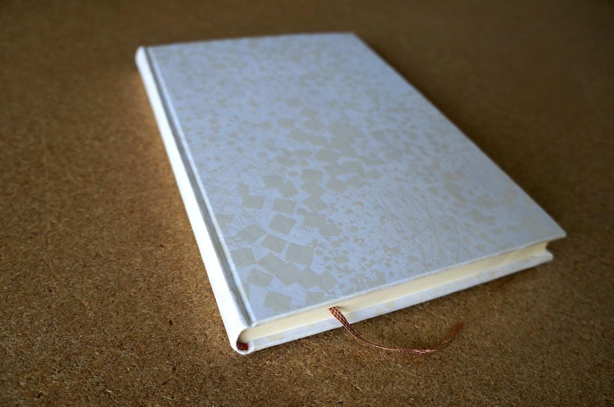 表紙に白ギラの伝統柄がプリントされた白鳥の子紙を使った手製本の丸背上製本ノート