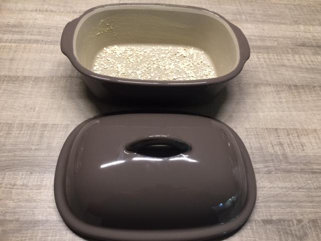 Fette deinen Ofenmeister mit etwas Backtrennmittel oder Rapsöl aus und streue den Brotbacktopf aus Ton mit Haferflocken aus...
