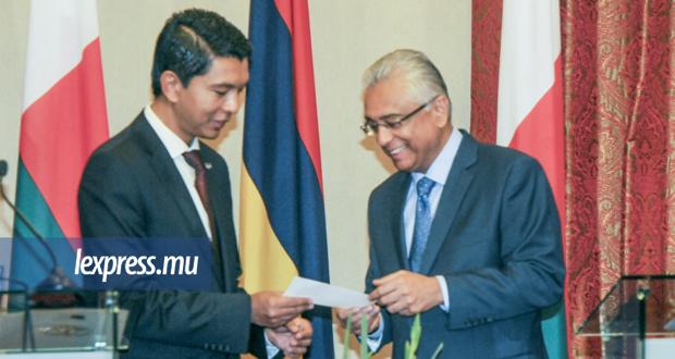 Le PM remettant au président malgache un chèque de 100 000 dollars contre la rougeole, lundi 11 mars.