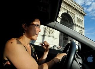 En voiture sur la Place de l'Etoile à Paris, avec l'Arc de Triomphe dans le fond