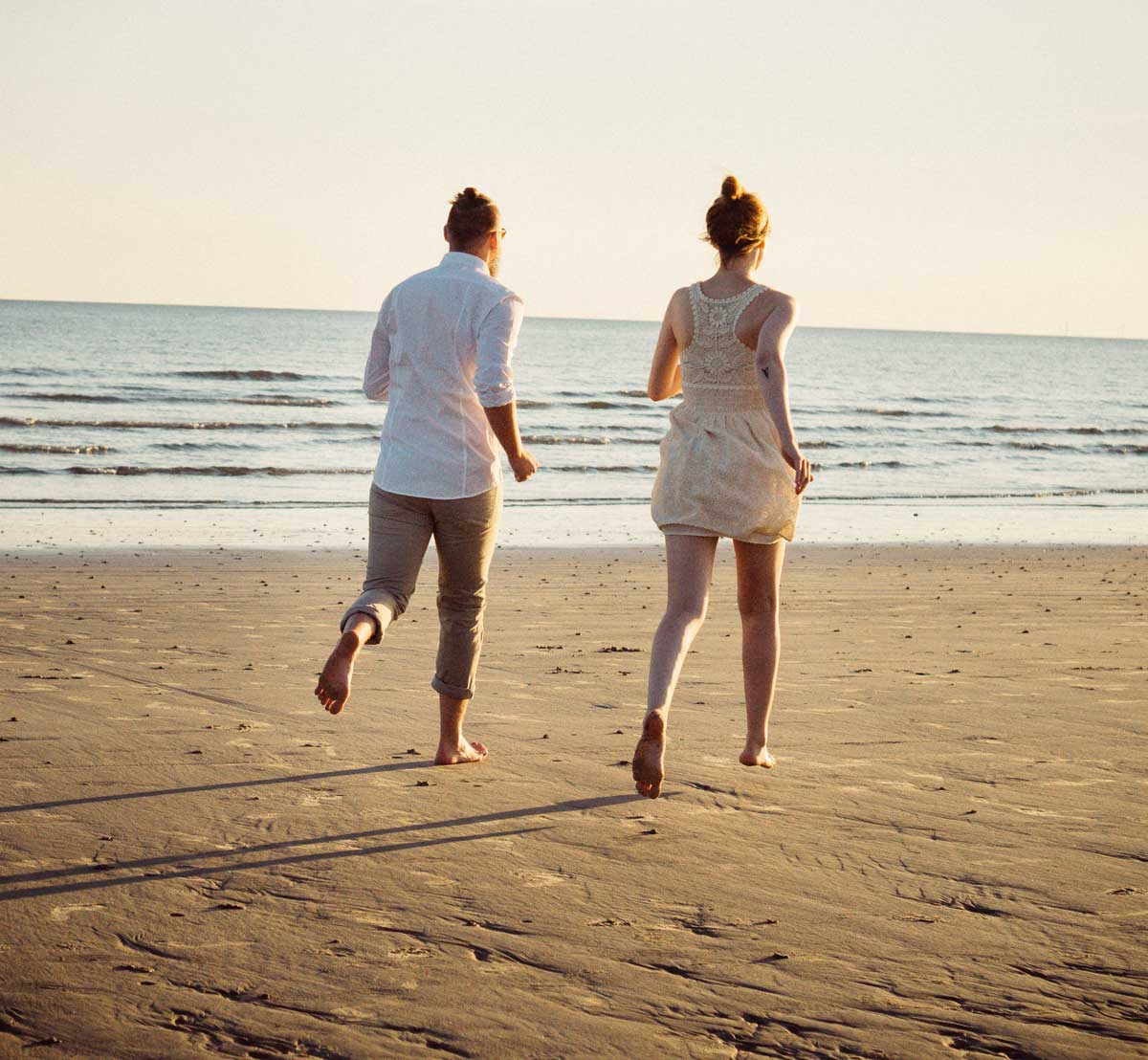 ©️benjamin wojcik photography - Fotograf Dortmund: Mann und Frau laufen am Strand
