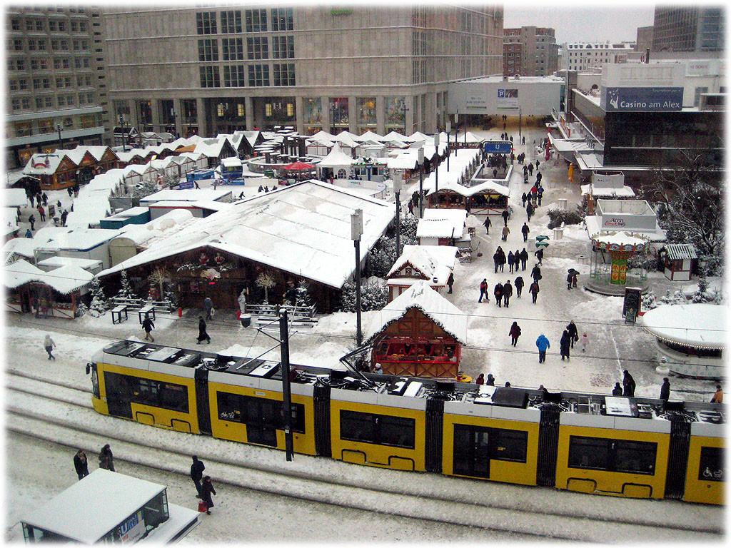 Bilder von der Tram Flexity, wie sie über den verschneiten Alexanderplatz fährt. Die Tram Flexity ähnelt sehr der Comicfigur Homer Simpson. Bilderbuch Berlin. Bilder aus der Geschichte der Hauptstadt.