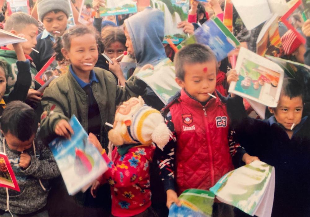 ラリポップ(あめ玉)をしゃぶりながらプレゼントに喜ぶ子どもたち。