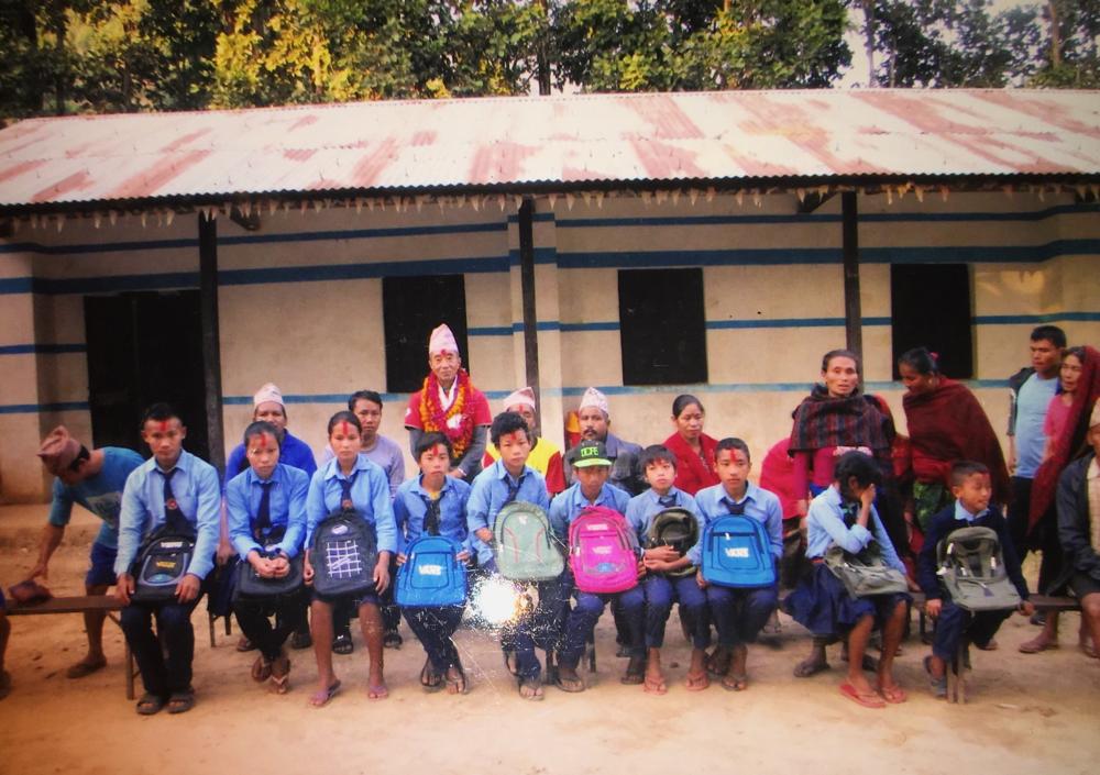 経済的に問題を抱えている子供達に文具(このカバンの中に入っています)とかばんのプレゼント。各生徒の後ろに親も参加してくれました。2018.12.1. ディルジェ村のジャナブリア校で