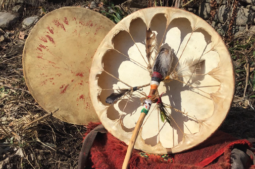 Mit Federn geschmückte Schamanentrommeln auf einer Wiese