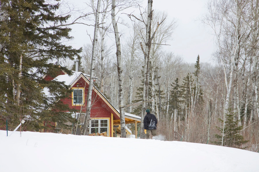 Wright Loft: A view to the garage, woodshop and loft space through the trees and the snow.