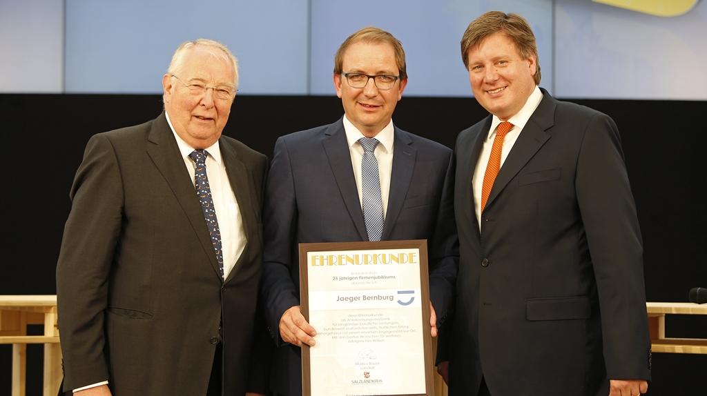 Firmengründer Hans Jaeger (l.)und sein Sohn, der heutige Gesellschafter Johann Jaeger erhalten vom Landrat Markus Bauer (Mitte) die Ehrenurkunde.