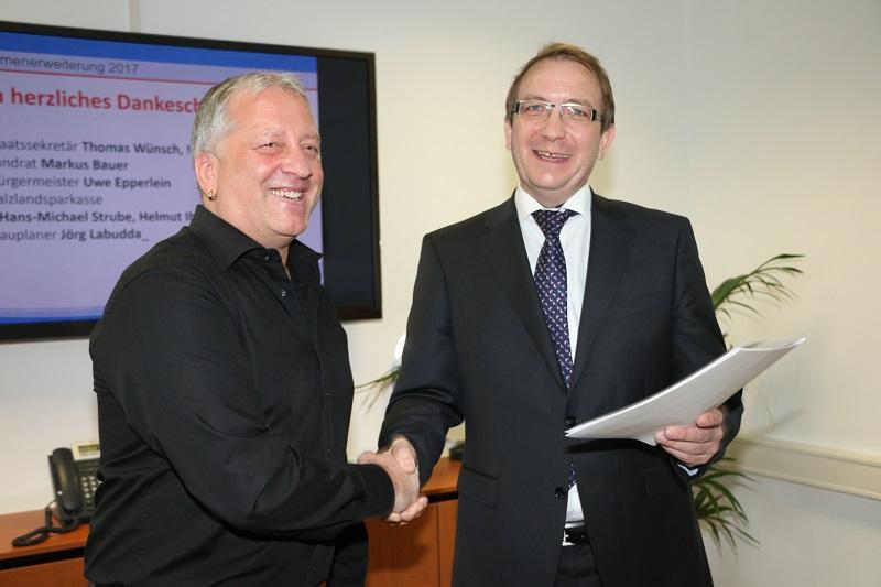 Foto: Salzlandkreis, Alexandra Koch - Landrat Markus Bauer übergibt die Baugenehmigung an Ralf Möller, Geschäftsführer des Unternehmens