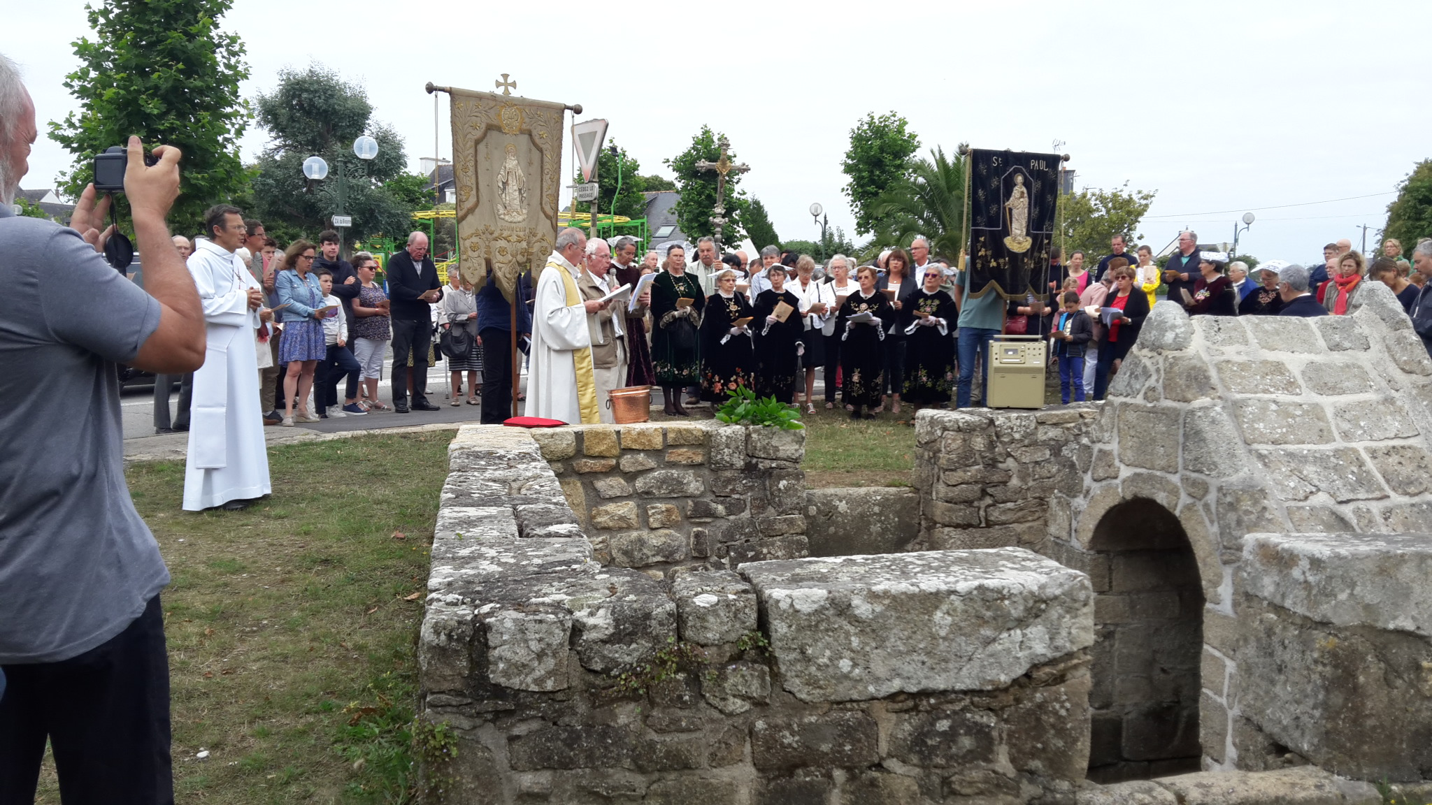 Le Père Michel Ezan accueille les fidèles à la fontaine du Pontoir