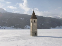 Das versunkene Dorf im Winter: der Grauner Kirchturm umringt vom Eis.