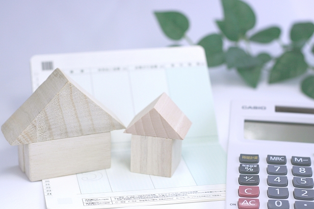 積み木の家が2つ、通帳、電卓の写真