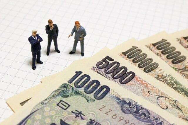 スーツを着た男性3人の人形と紙幣の写真