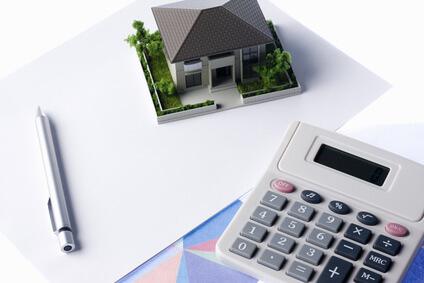 家と電卓とボールペンの写真