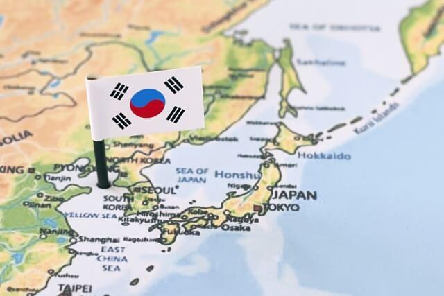日本を中心とした地図と、韓国の国旗の写真