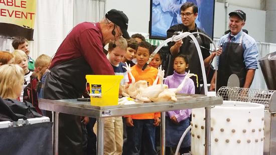 マザーアースニューズフェアであらゆる年代の聴衆に食肉加工のデモをするジョエル・サラティン