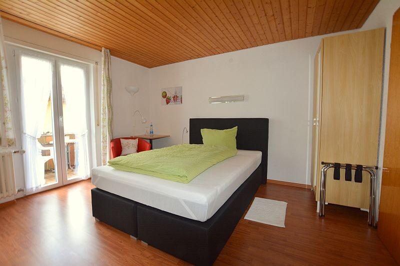 Einzelzimmer mit Laminatboden und King Size Boxspringbett