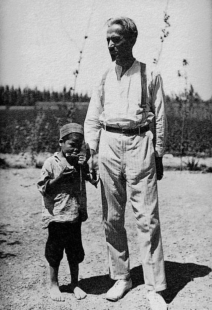 Ernst Jakob Christoffel steht mit einem Kind auf einem Feld