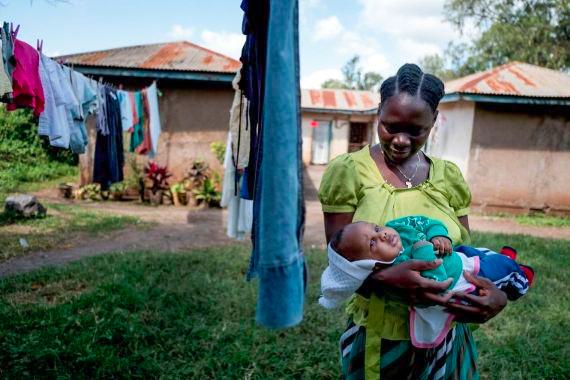 Frau mit Kind im Arm steht vor voller Wäscheleine