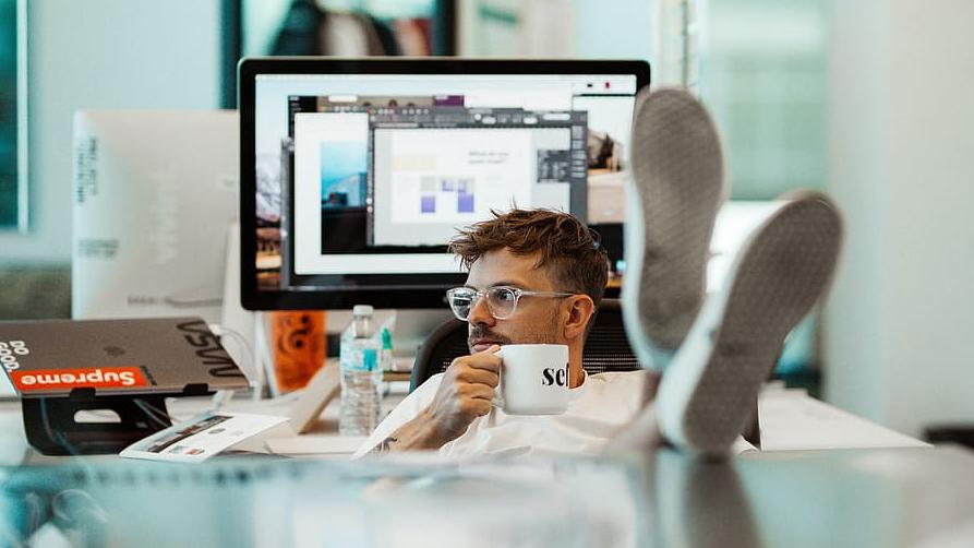 Junger Mann sitzt im Büro mit vollen Schreibtisch, , in der Hand eine Tasse, die Füße auf dem Tisch und sieht aus dem Fenster