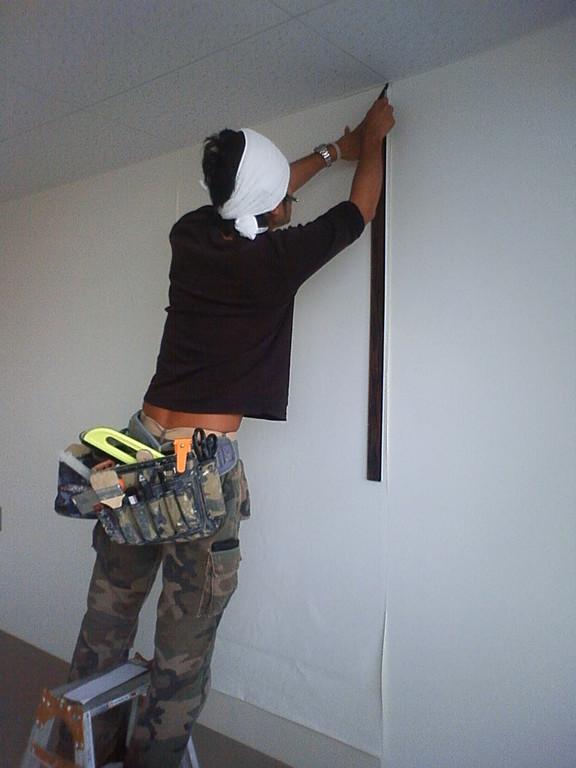 壁紙を一部剥がし、下地にある壁の凹凸をなくす作業です。