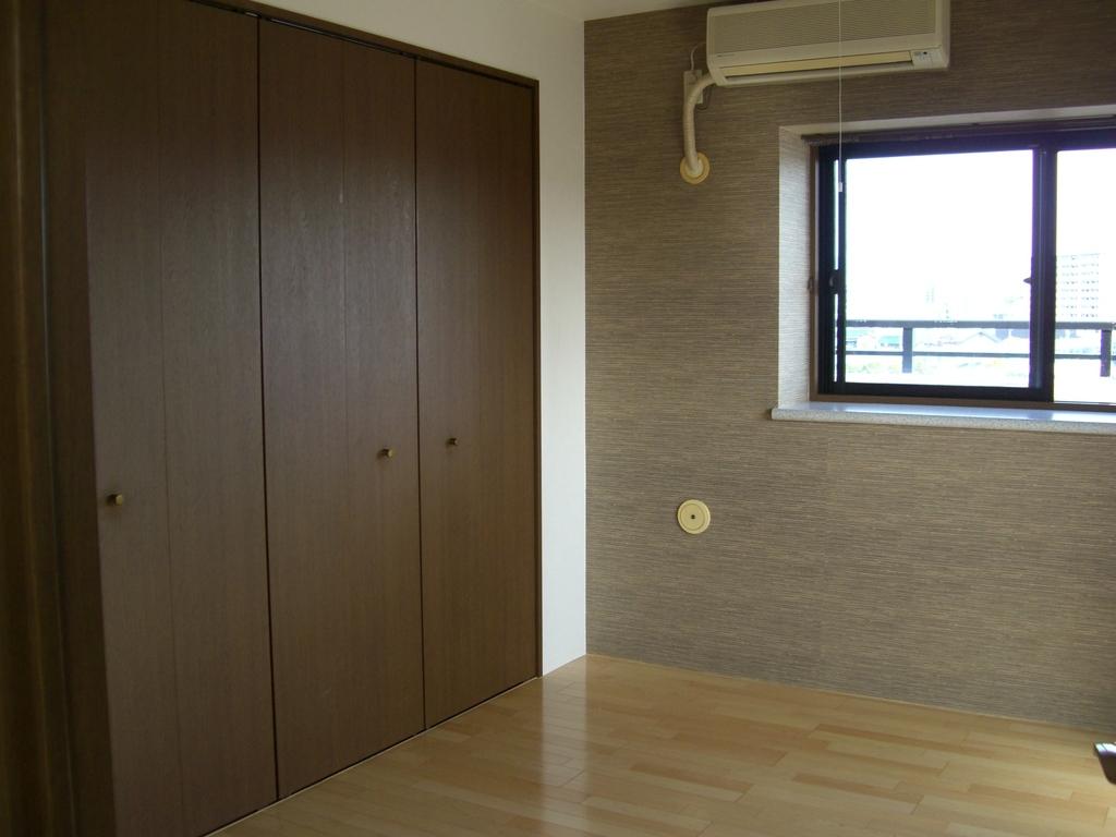 洋室奧の壁にアクセントクロスを使用。床の光沢とマッチします。